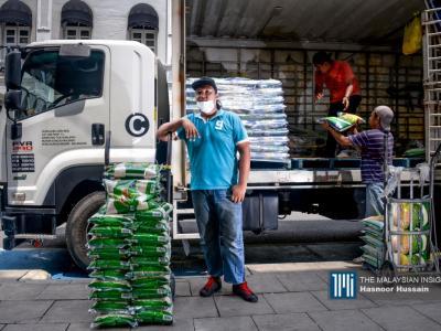 在实施行动限制令后,民众涌入超市抢购米粮,不少大型的超市和小规模的杂货店,几乎天天都要靠搬运工人补货,今年22岁的努莱米雅敏,在雪州大港忙碌的补充白米给商家。(摄影:Hasnoor Hussain)