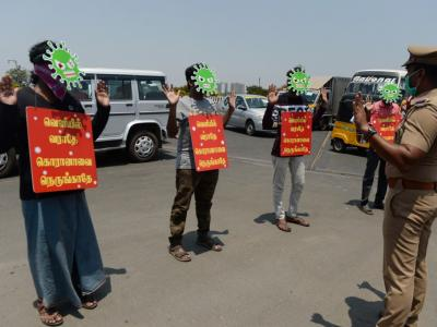 Men wearing masks depicting a coronavirus and placards reading 'Don't come out, don't go near to corona' as punishment enforced by the police for breaking a nationwide government-imposed lockdown in Chennai. – AFP pic, April 2, 2020.