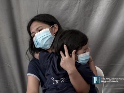 一名印尼妈妈在临时扣留营中安慰着自己的小孩。(摄影:Najjua Zulkefli)