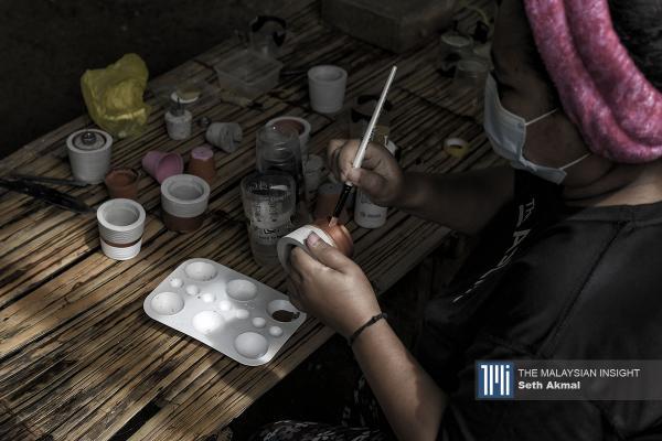 Ayu Jemeni memakai pelitup muka semasa melukis pasu bunga di rumahnya di Kampung Orang Asli di Serendah, Selangor. – Gambar The Malaysian Insight oleh Seth Akmal, 16 Julai, 2020.