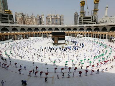 Pilgrims holding coloured umbrellas and matching coloured rings separating them as a Covid-19 coronavirus pandemic measure while circumambulating around the Kaaba, Islam's holiest shrine, at the centre of the Grand Mosque in f Mecca, at the start of the annual haj pilgrimage on Wednesday. – AFP pic, July 31, 2020.