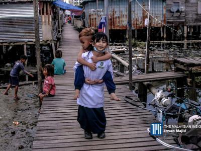 Seorang kanak-kanak perempuan tersenyum ketika menggendong adiknya di Kampung Sembulan, Kota Kinabalu, Sabah. - Gambar The Malaysian Insight oleh Irwan Majid, 20 September, 2020.