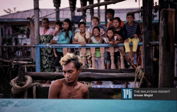 汶汶岛上的村民们向乘船抵达的志愿者挥手致意。(摄影:Irwan Majid)