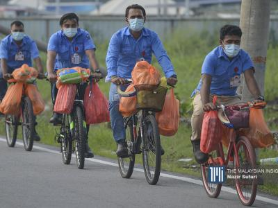 Top Glove workers cycling back to their dorms in Meru, Klang, Selangor after stocking up on necessities needed to wait out the EMCO set to end on November 30. - The Malaysian Insight pic by Nazir Sufari, November 17, 2020.
