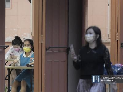 A teacher wears a face mask while walking in front of an examination hall at SMK Convent Bukit Nanas in Kuala Lumpur. - The Malaysian Insight pic by Seth Akmal, February 22, 2021.