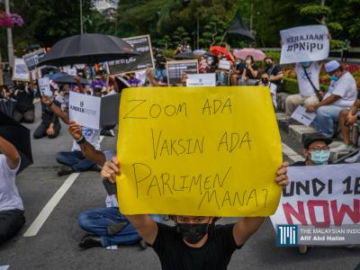 Protesters holding placards as they sit outside the Parliament building to protest the Election Commission's (EC) delay in allowing 18-year-olds to vote in Kuala Lumpur. – The Malaysian Insight pic by Afif Abd Halim, March 27, 2021.