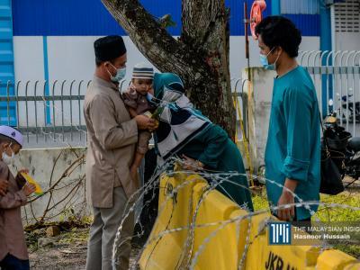 Seorang wanita mencium anak saudaranya ketika mereka berkumpul di sempadan Selangor-Negeri Sembilan di Bandar Bukit Mahkota semasa sambutan Aidilfitri. Kerajaan melaksanakan PKP dengan larangan rentas negeri dan daerah di seluruh negara buat kali ketiga. – Gambar The Malaysian Insight oleh Hasnoor Hussain, 13 Mei, 2021.