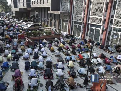 Jemaah menunaikan solat Aidilfitri di luar kawasan  Masjid Jamek Kampung Baru di Kuala Lumpur. – Gambar The Malaysian Insight oleh Seth Akmal, 13 Mei, 2021.