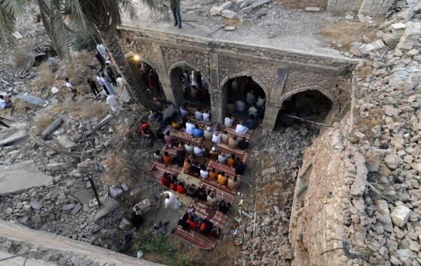 伊拉克第二大城摩苏尔(Mosul)东部地区的居民在庆祝开斋节,他们受损的Umayyad清真寺祈祷。(图:法新社)
