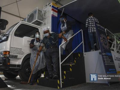 在吉隆坡甘榜Muhibbah人民组屋的疫苗流动卡车,医务人员协助一名刚刚接种第一剂疫苗的银发族走下卡车。(摄影:Seth Akmal)