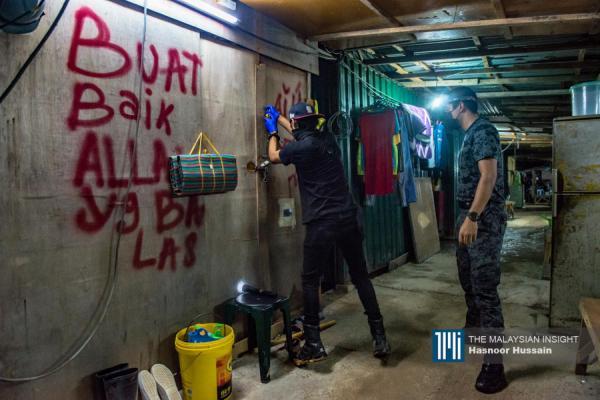Pegawai Imigresen memecah pintu hostel pekerja binaan semasa serbuan oleh Jabatan Imigresen di hostel pekerja binaan di Bandar Baru Lembah Selatan Dengkil di Selangor. – Gambar The Malaysian Insight oleh Hasnoor Hussain, 21 Jun, 2021.