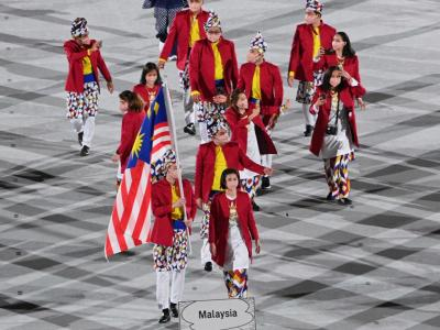 Malaysia's flag bearer Lee Zii Jia and the delegation parade during the opening ceremony of the Tokyo Olympics, at the Olympic Stadium in Tokyo. – AFP pic, July 24, 2021.