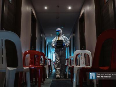 一名大马国际人道救援组织志愿者在吉隆坡 Travelodge 市中心隔离中心为一名患者提供食物。(摄影:Afif Abd Halim)