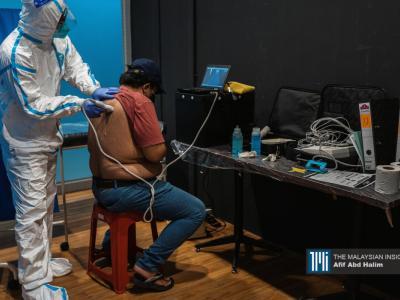 医生检查冠病患者的症状,需要进一步治疗的患者会被送到沙登农业博览馆(MAEPS)。(摄影:Afif Abd Halim)