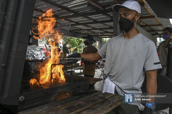 GrillbodoBackyard owner Zahrein Mustaffa prepares packs of grilled meat for takeaway, in Kampung Baru, Kuala Lumpur. - The Malaysian Insight pic by Seth Akmal, September 8, 2021.