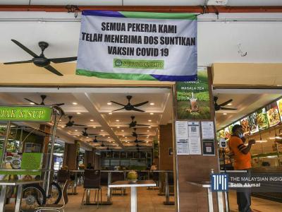 Pemilik restoran di Kuala Lumpur menggantung bannner untuk memaklumkan pelanggan bahawa pekerja mereka sudah menerima vaksin sepenuhnya.– Gambar The Malaysian Insight oleh Seth Akmal, 8 September, 2021.