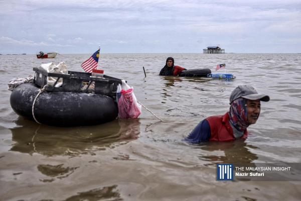男人们用脚寻找海螺,感受埋在海泥里的生物。(摄影:Nazir Sufari )