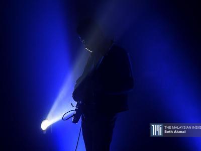 吉他手戴着口罩,在进行独自演奏的排练。(摄影:Seth Akmal)