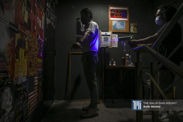 工作人员在现场直播表演彩排前,向一名乐队成员用纳米喷雾枪喷洒消毒剂。(摄影:Seth Akmal)