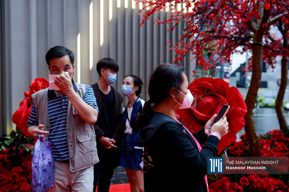 Tourists wearing masks to protect themselves from the Wuhan virus seen in Bukit Bintang, Kuala Lumpur, last month. The absence of Chinese nationals' spending power will be felt in Asian countries that are popular tourism destinations, Malaysia among them. – The Malaysian Insight file pic, February 8, 2020.