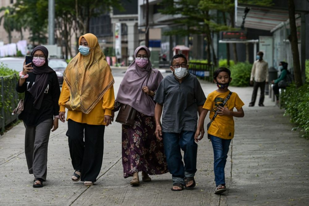 Pedestrians on a Kuala Lumpur street a day after the king consented to the declaration of a state of emergency on January 12. – AFP pic, March 1, 2021.